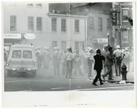 A crowd of police officers in gas masks at 14th and U Street