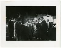 A group of men gather on the street at night.