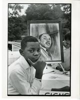 A young boy sits at a table with a painting of Martin Luther King, Jr. in the background