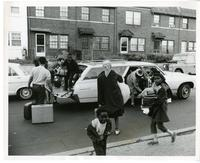 A group of adults and children unload belongings from a car