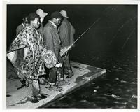 A group of men with radios and flashlights look at water