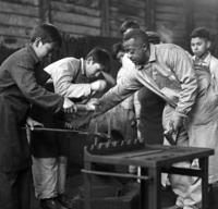 Peace Corps Volunteer Walter White instructs a forging class at the ship building school in Valdivia, Chile