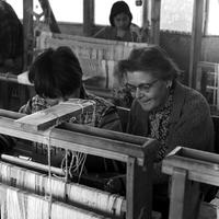 Peace Corps Volunteer Blanch Everhard sits next to a student at a loom during her weaving class at the Instituto de Educación Rural in Curicó, Chile