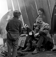 Peace Corps Volunteer Gage Skinner in traditional dress sitting with Mapuche peoples, Chile