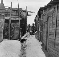 Children carrying a bucket through urban slums in the Población Colo Colo, Nueva Palena, Chile