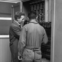 Peace Corps Volunteer Charles Murray and an unidentified man working on electrical equipment at the Universidad Técnica del Estado in Temuco, Chile