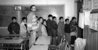 Peace Corps Volunteer Rex Jackson posing with his fourth grade students in a classroom, Melipeuco, Chile