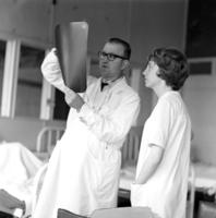 Peace Corps Volunteer nurse Susan Black and a male doctor inspecting an x-ray at the John F. Kennedy Hospital in Valdivia, Chile