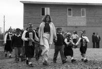 Peace Corps Volunteer Amanda Herrera walking hand-in-hand with a group of Mapuche children going to the opening of the Internado Centro Cultural Mapuche, Temuco, Chile