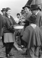 Peace Corps Volunteer Janie Beers presents a bowl of food to locals, Chile